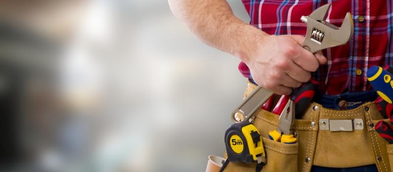 Arbeiter mit Schraubenschlüssel und Werkzeuggürtel